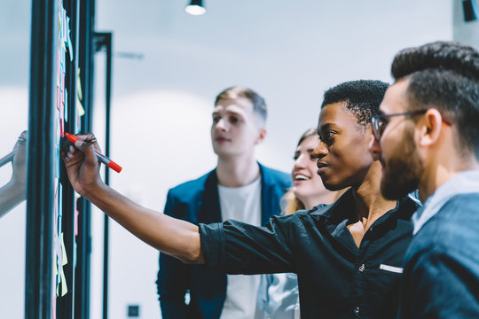 Group of diverse employees concentrated on idea during meeting in office, African American men worker in formal wear writing information on sticky note while brainstorming together with colleagues
