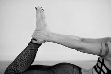 Anonymous yoga woman body detail practicing in studio photographed in black and white.  Bow Pose or Dhanurasana