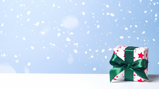 Christmas gift box with green ribbon bow in snow on blue background. Christmas, New Year, winter holidays concept