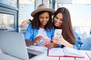 Cheerful multiracial female best friend share multimedia files on smartphones spending free time together,smiling hipster girls synchronizing telephone sending photos and video sitting at cafe.