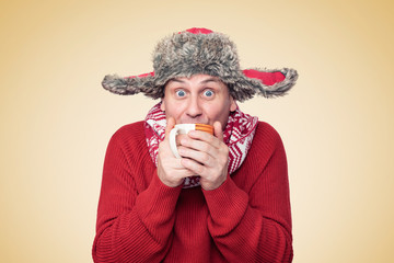 Funny happy man in a red sweater, scarf and hat holds in his hands a mug with a hot drink