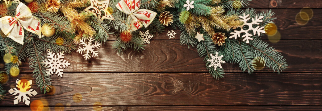 fir branches with Christmas decor on old dark wooden background