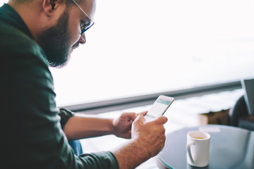 Cropped image of pensive bearded man in eyewear making peyment online via free high speed internet connection on smartphone sitting in cafe with mug of tea.Blogger share media in networks on cellular