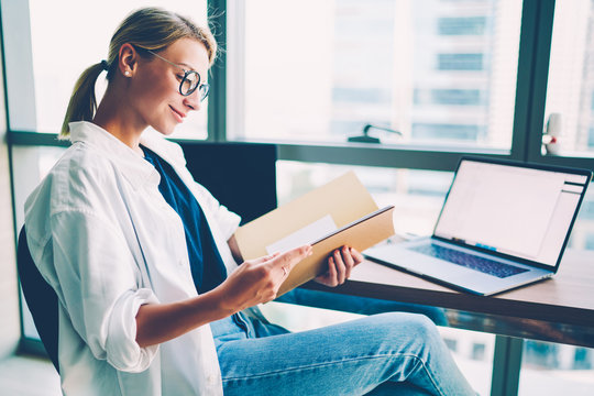Cheerful young woman in eyeglasses satisfied hight financial reports reading in folder sitting at desktop with digital computer gadget with blank screen area for advertising working at office building