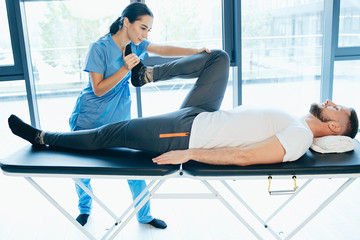 man treat lumbar disc. man lying on massage table while his physical therapist doing special exercises for physical therapy for sciatica and pinched nerve problems