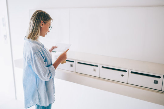 Young caucasian blonde woman standing with correspondent in hand near white metal letterboxes,casually dressed hipster girl reading documents get by postal delivery in white envelope standing in hall