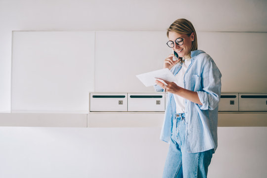 Positive casually dressed woman having telephone conversation holding new letter from postal delivery, smiling hipster girl calling to friend for saying thanks for received greeting postcard