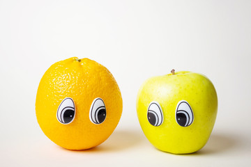 Orange and green apple with eyes. Orange and apple are looking at each other. Funny picture of fruits. The concept of friendship, sympathy, love. Light background, place for text.