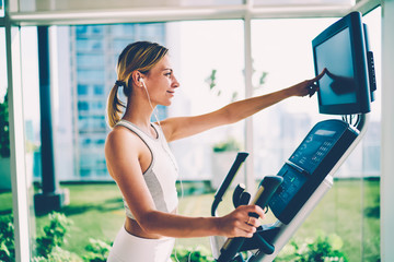 Young beautiful happy female person enjoying making exercises on bike for supporting healthy lifestyle and fit body. Pretty positive woman listening to music while training on cross trainer in gym