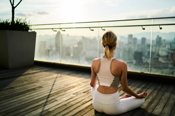 In de dag Ontspanning Sports woman in white track suit sitting in lotus pose meditating and feeling calm in big city, back view of slim woman with perfect figure having yoga training on building rooftop relaxing in morning