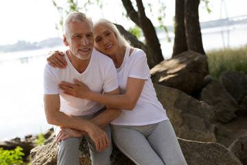Man and woman sitting on the rocks in sporty clothes stock photo