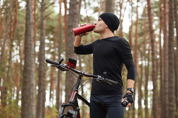 Horizontal outdoor picture of good fit sportsman drinking water from red bottle, having short stop, riding his bicycle in forest alone, sticking to healthy lifestyle. People, sport and nature concept.