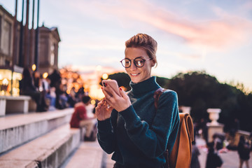 Positive young hipster girl typing text message using 4g wireless for networking and online communication, happy female tourist in spectacles blogging creating publication about tourism and trip