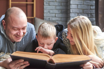 father, son and daughter read a book in bed