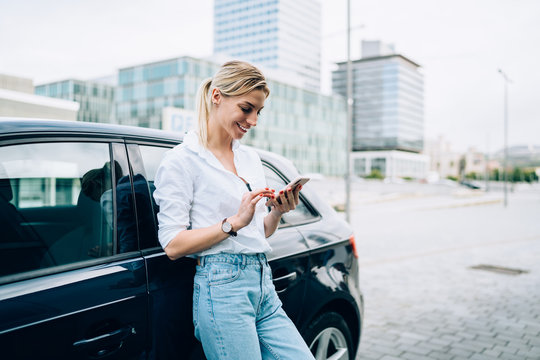 Smiling woman with smartphone standing beside car
