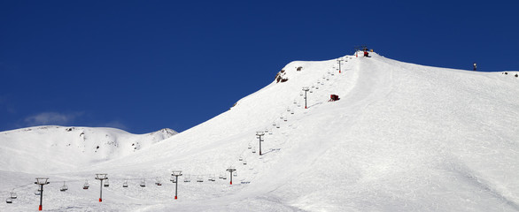 Fototapete - Ski slope with ropeway at sun winter day