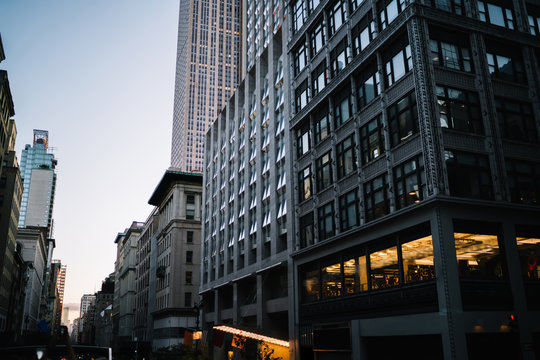 Evening view of tall building exterior with real estate for commercial and residential rent in midtown, urban architecture with high skyscrapers and old construction fronts on street in New York
