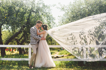 Caucasian couple in love bride and groom standing in embrace near wooden white, rural fence in park an apple orchard. theme is wedding portrait and beautiful wedding white dress with long veil