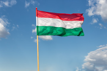 Hungary national flag waving on wind at blue sky background