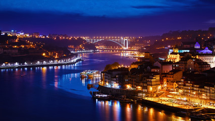 Fototapete - Porto, Portugal. Evening sunset panoramic view at nighttime town. Coastline of river Douro with reflections of illumination in water and picturesque clouds on blue sky.
