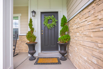 Gray front door of a home with green wreath and flanked by tall potted plants