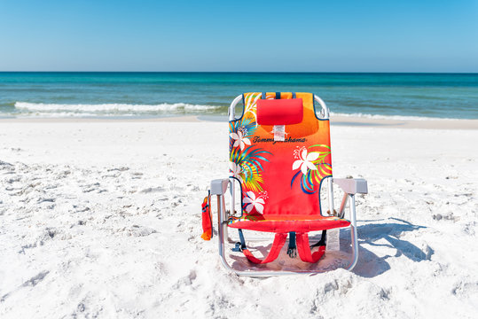 Santa Rosa Beach, USA - April 25, 2018: One beach chair Tommy Bahama brand empty during sunny day in Florida panhandle gulf of mexico with ocean waves, landscape, white sand