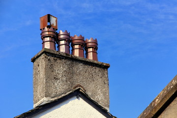 Row of four old ornate ceramic chimney pots on a rooftop chimney stack, with blue sky