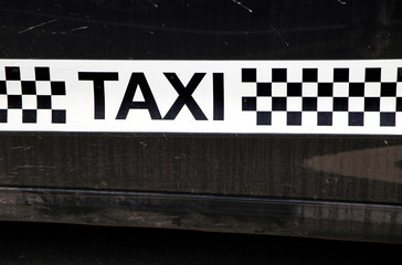Taxi logo with checked or chequerboard pattern in black and white, on the side of a black cab or car for hire