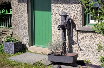 Vintage cast iron water pump outside a house with green door and window frames, in a rural rustic setting on a sunny day
