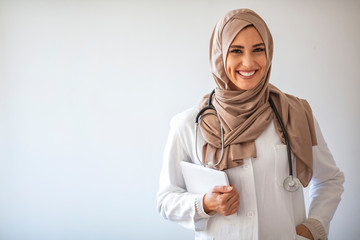 A female Muslim medical doctor stands proudly and smiles for the camera as she carries a medical record under her arm. Confident Muslim female doctor standing inside hospital