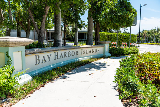 Bal Harbour, USA - May 8, 2018: Bay Harbor Islands in Miami Florida with green plants and sidewalk by sign entrance to city