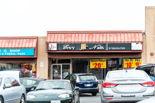 Takoma Park, USA - April 1, 2018: Downtown area of city in Maryland, MD with strip shopping mall and cars parked in parking lot with stores Envy Nails
