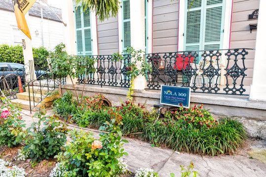 New Orleans, USA - April 23, 2018: Old town Royal street in Louisiana famous city with green shutters colors on house building and balcony with plants in front yard garden and celebration sign