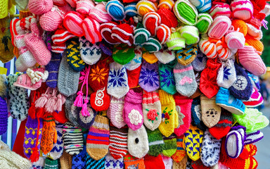 Colorful handmade socks and mittens on stalls of Christmas market in Riga of Latvia winter. Street Xmas and holiday fair in European city or town. Advent Decoration with Crafts Items on Bazaar