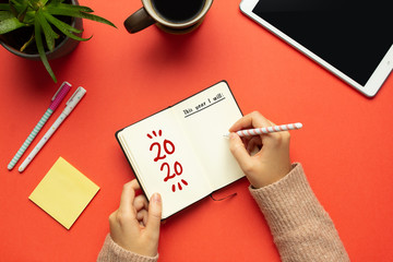 Stock photo of a young woman hands writing in a 2020 new year notebook with list of goals and objects on red background