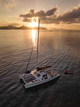 Beautiful view to catamaran boat in Seychelles bay during sunset from a drone, travel to a tropical island and boat tour concept