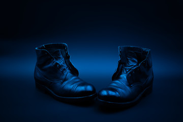 A pair of old worn shiny black boots which are missing their laces. The boots are isolated on a dark background and decorated with a string of lights. Wall mural