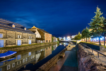 Night view of the Otaru canal and an old warehouse next to the port in Otaru, Japan.