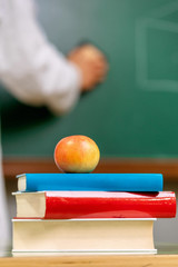 Closeup view, of a teacher desk with a pile of books and a red apple in front of a chalkboard .