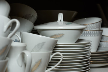Stack of coffee cups and plates in shadow
