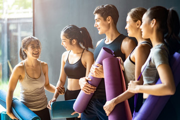 Poster Ontspanning Group of diversity ethnic people holding Yoga mat talking together with smile. Asian girl laughing with funny face after finish training class. Happy and relax time in group of best friend in Gym.
