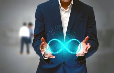 DevOps concept, an IT engineer holding the glowing devops symbol that illustrates the software development practices that automates the continuous development, build integration and deployment process