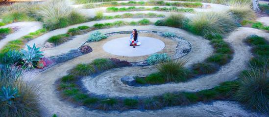 Foto op Aluminium Spiraal Frau sitzt in einem Labyrinth