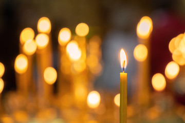 Candle light in christian church warm tone with dark black background