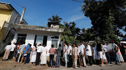 People stand in a line to cast their votes during the presidential election, at a polling station in Colombo