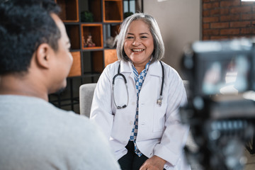 doctor speaking and see to the patient and recording with camera