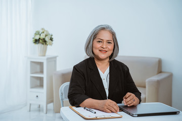 Confident senior business woman when sitting on the work desk