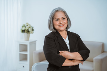 Confident senior business woman standing with crossed hands