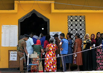 A police offier is seen as people stand in a line to cast their vote during the presidential election in Colombo
