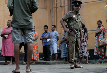 A police officer looks on as people stand in a line to cast their vote during the presidential election in Colombo